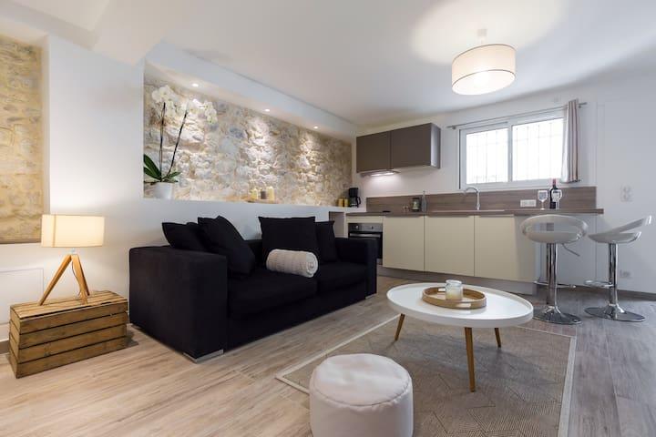 Le salon avec son canapé et un aperçu de la cuisine/The living room with its sofa and kitchen.