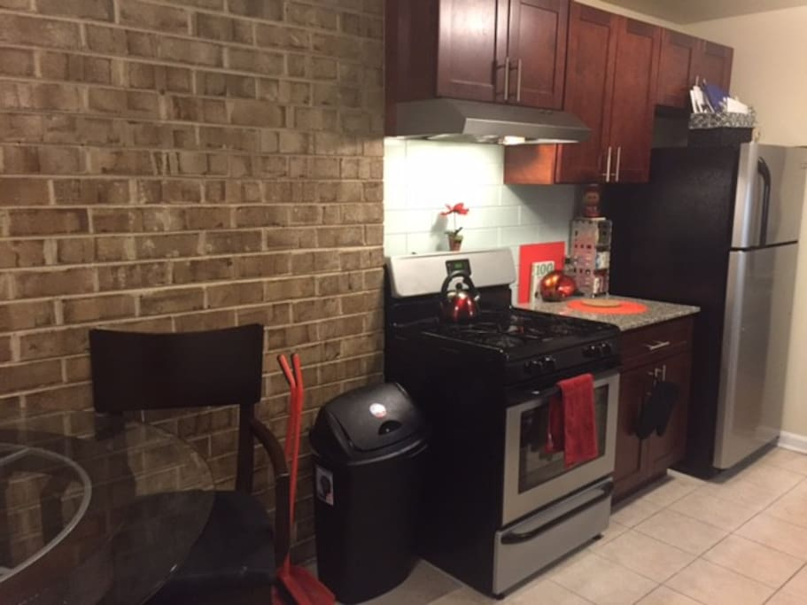 Exposed brick wall, granite counter tops, glass backsplash in kitchen.