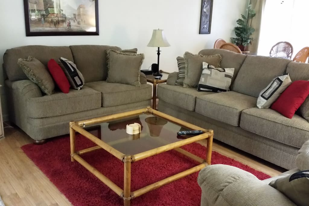 Comfortable living room with couch, loveseat, and rocker recliner. Flat screen smart TV.