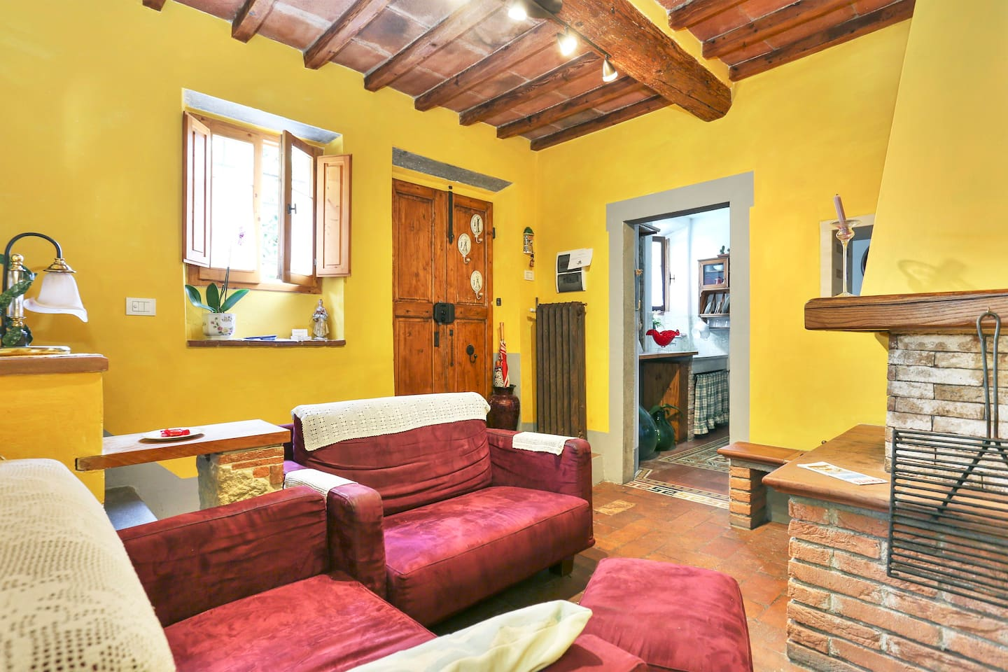 First floor living room fireplace with exposed beams. Salotto con camino, cotto e travi a vista