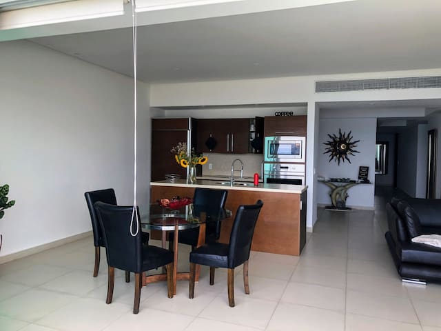 Main area - kitchen, dining and living room with a front terrace looking at the ocean