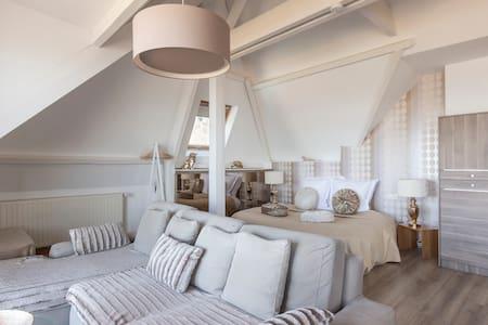 Suite de luxe avec balcon face à la mer, lit rond, salon, kitchenette, salle de bain vue mer avec baignoire et douche