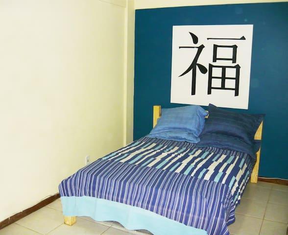 Quarto com cama de casal, Tv, Ar condicionado e ventilador de teto.