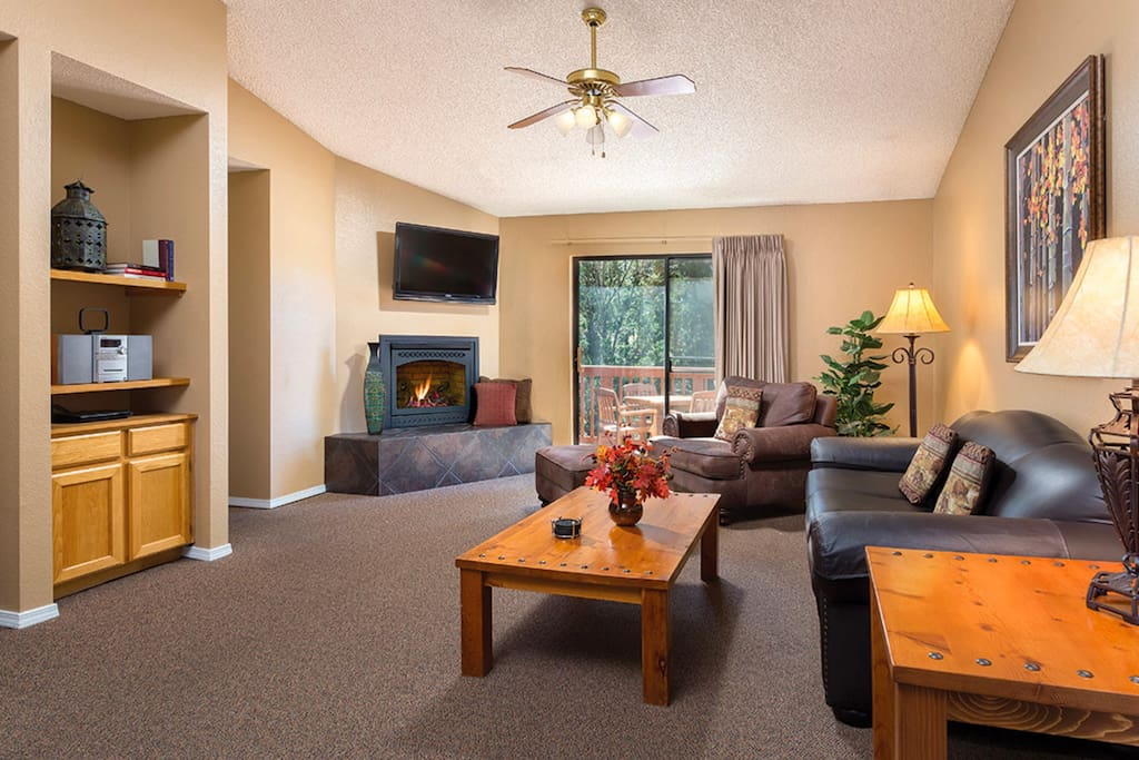 Relax in the living room with cozy couches, a fireplace, and a flat-screen TV