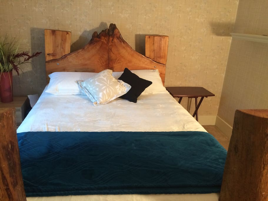Queen size bed in bedroom 3 with unique driftwood bad frame