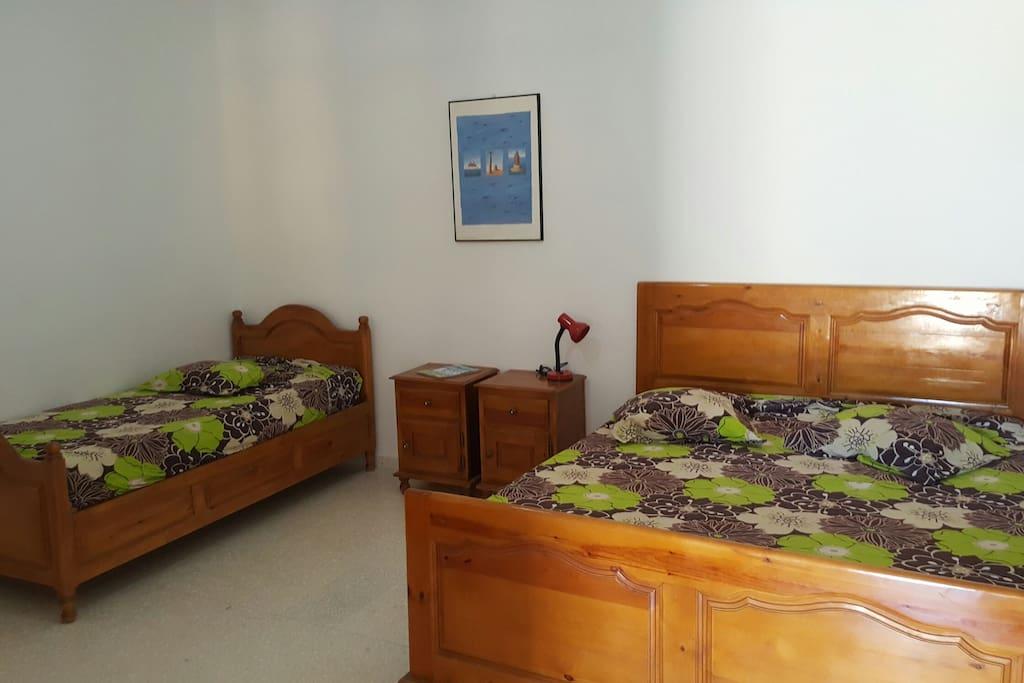 Une grande chambre à coucher avec un lit double et un lit simple ( plus deux matelas supplémentaires).