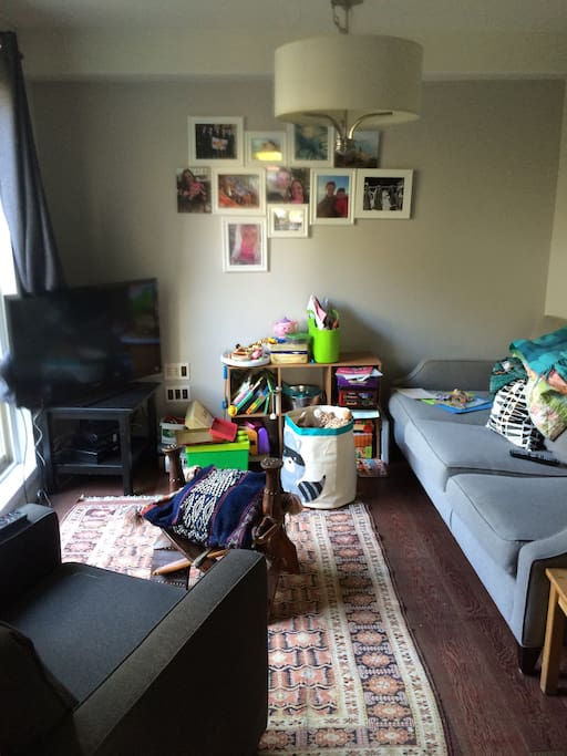 Den with tv sofa and children's toys (toddler and infant) door to fully enclosed back patio