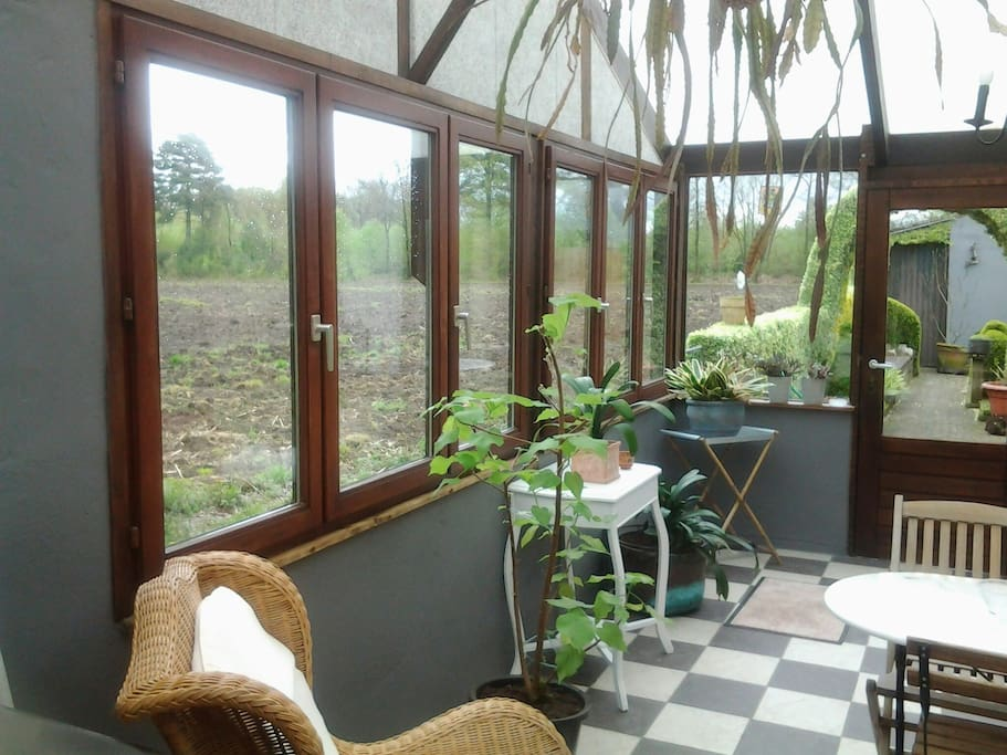 veranda,  met uitzicht over veld en tuintje
