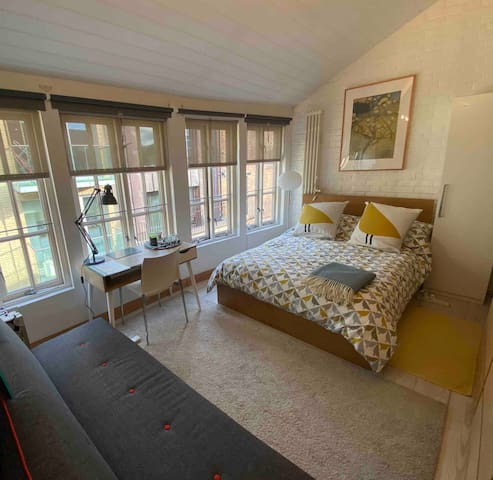 Guest double bedroom with desk, drawers and coatrack. Plenty of soft light through the East facing windows. This bedroom looks over a quiet cul-de-sac so no traffic noise
