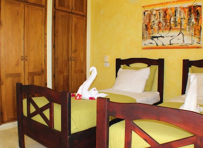 The yellow bedroom with single beds