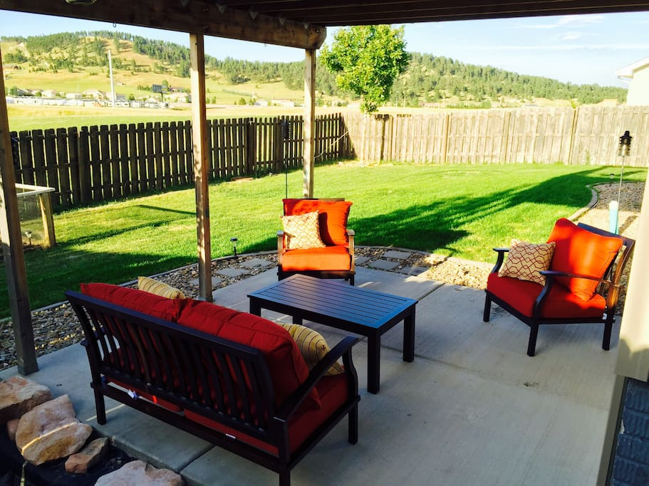Comfortable patio furniture and views of the hills on a summer night