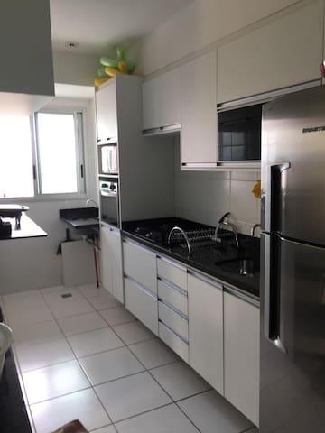 Cozinha com geladeira, filtro, micro-ondas, forno. Prato, talheres, copos, panelas.