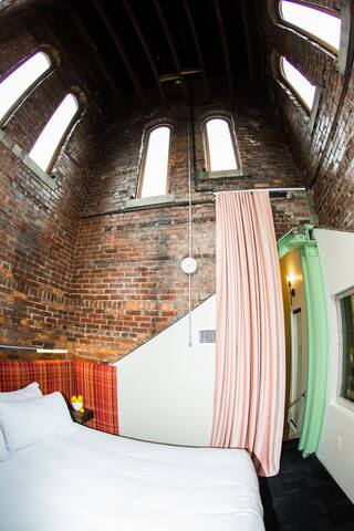 The bell tower windows allow for a unique view from this bedroom in the tower suite.