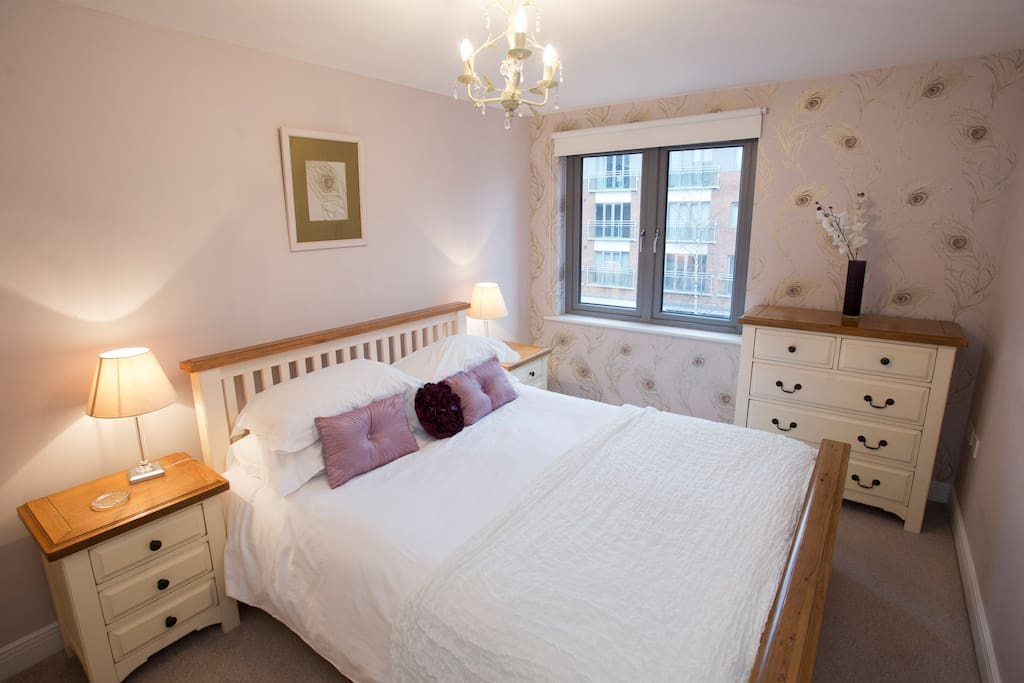 The lovely bedroom has a large king-size double bed, wardrobe, chest-of-drawers