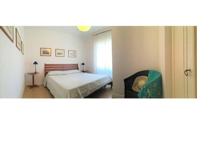 Camera da letto matrimoniale con ampia finestra con tapparelle, grande armadio, 2 comodini e prese per lato