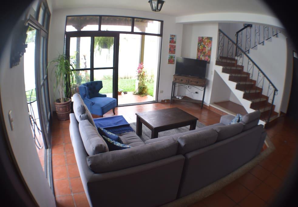 Living room includes huge couch, floor-to-ceiling window/doors, and big screen TV