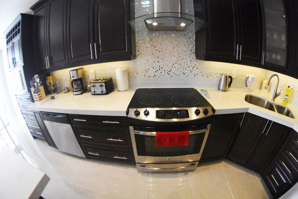 Slide In Kitchen Aid Stove with Convection Oven, Tall Maple Walnut Cabinets ,Glass Range Hood.