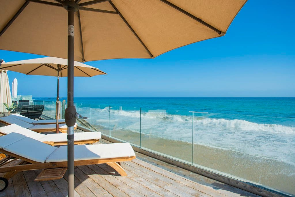 Situated right on the beach of the exclusive neighborhood in Malibu Colony. The property is one of the most sought-after rental properties available. Just steps below the deck is fresh sand and waves which lightly crash on to the beach shore.  The deck area has multiple lounge chairs and umbrellas, perfect for relaxing and catching some of the California golden sun.