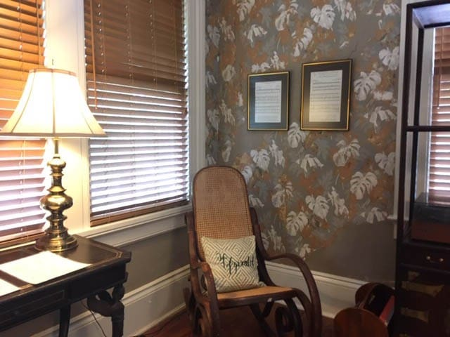 The living room and bedroom have the original historic wallpaper exposed in sections.