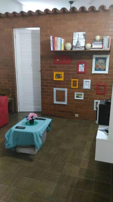 """Sala aconchegante com tv 32"""", sofá cama e mesa para refeições."""