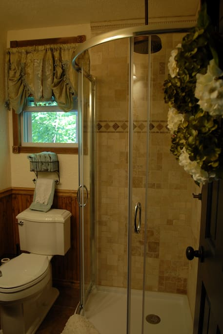 A beautifully tiled bathroom with a pedestal sink and glass doors shower