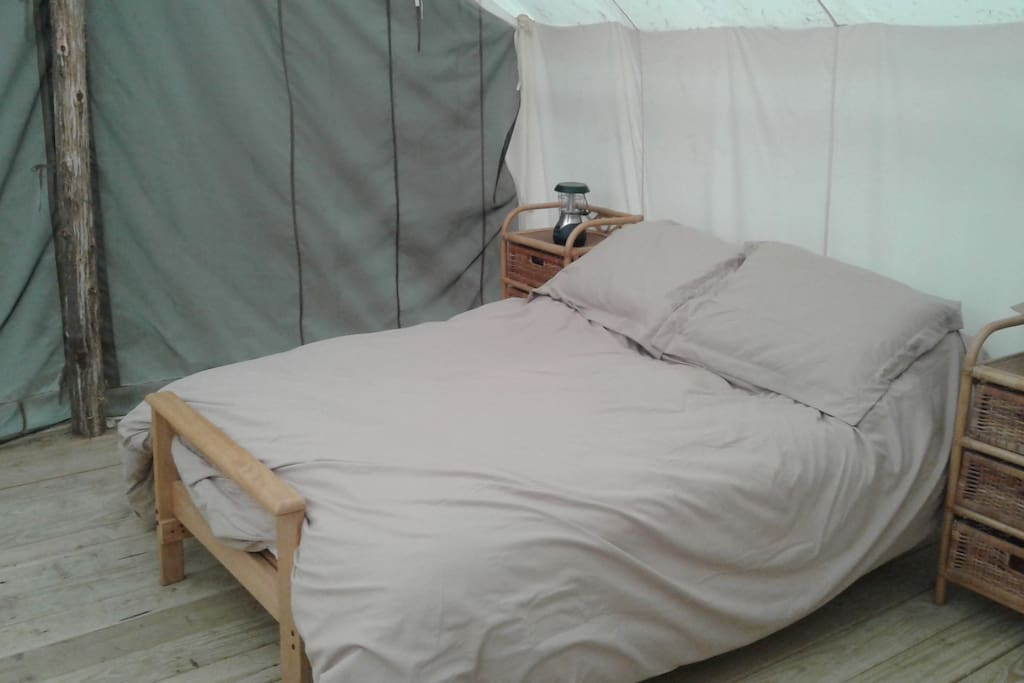 Cabin-style tent houses a full-sized futon bed with wool-topped mattress for added comfort. All bedding provided.