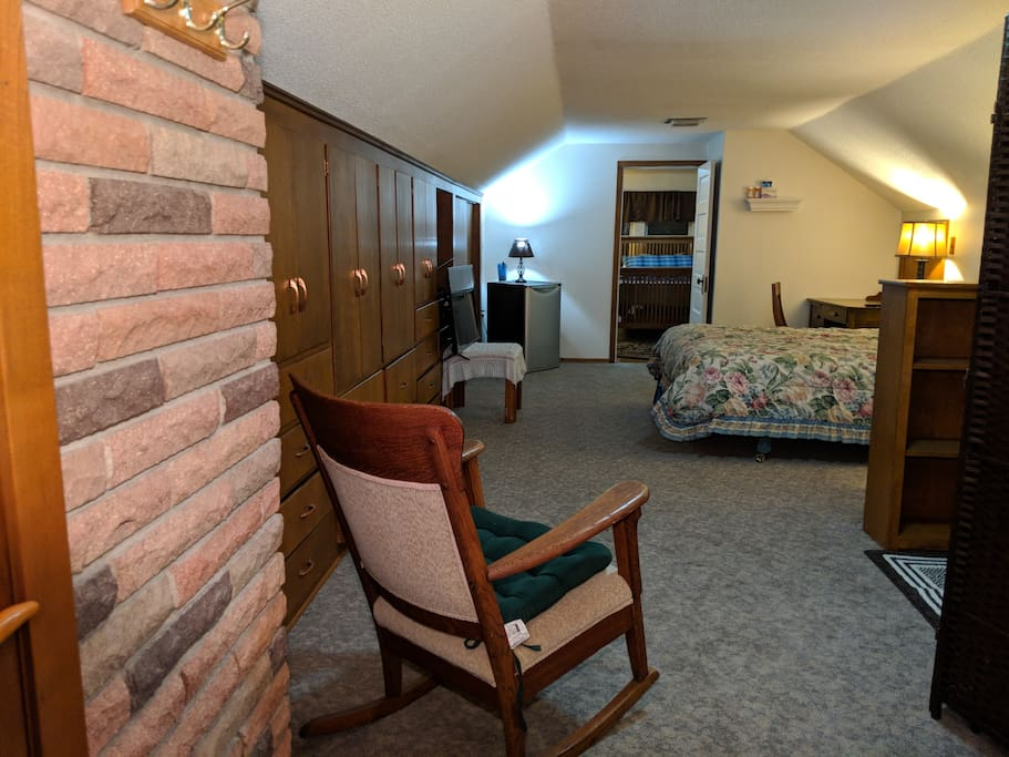 A view of the bedroom through open door & living room w/futon and single bed.
