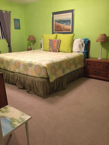 The master bedroom has a king size bed, a large walk in closet, a ceiling fan and a flat screen tv