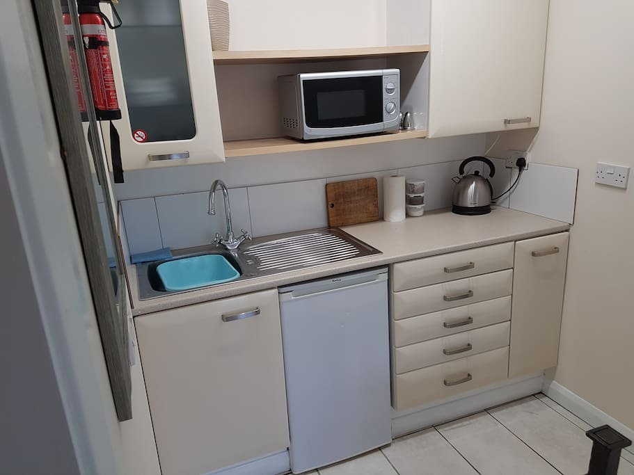 Food prep area with microwave, fridge, kettle and sink