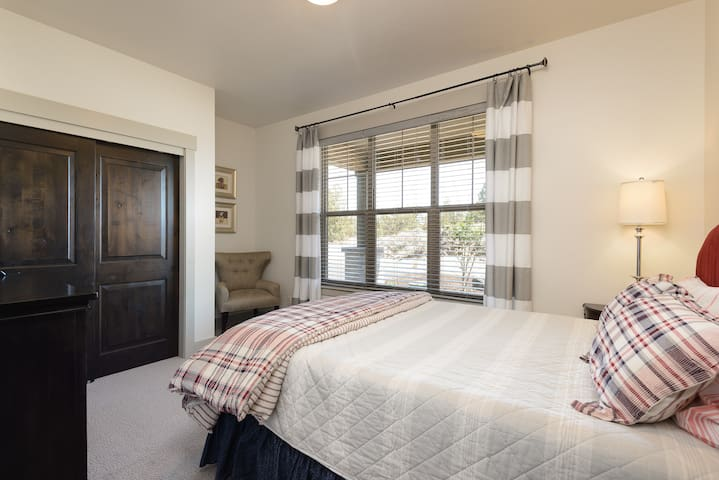 Second guest bedroom on main floor with comfortable queen bed and TV