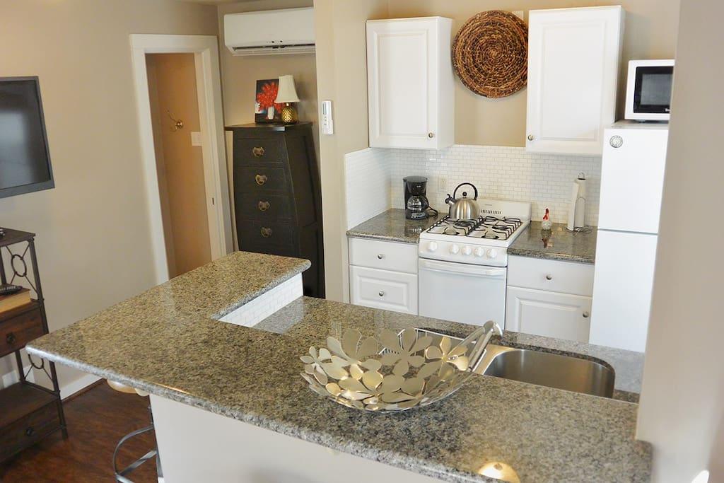 Nice kitchen with pots, pans, utensils, coffee pot & supplies.