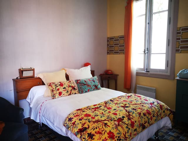 Grande chambre déco orange. Possibilité de rajouter un couchage 1 place d'appoint.