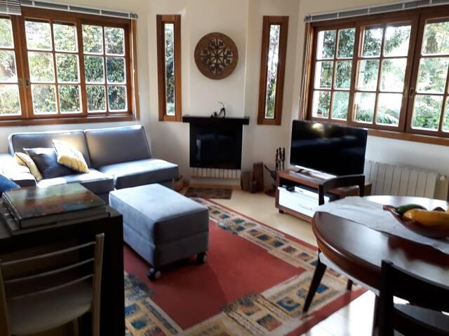 Sala de estar conjugada com sala de jantar, com mesa de quatro lugares, ampliável para seis lugares