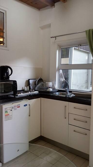 Cocina americana, encimera eléctrica, horno eléctrico y equipada con menaje.