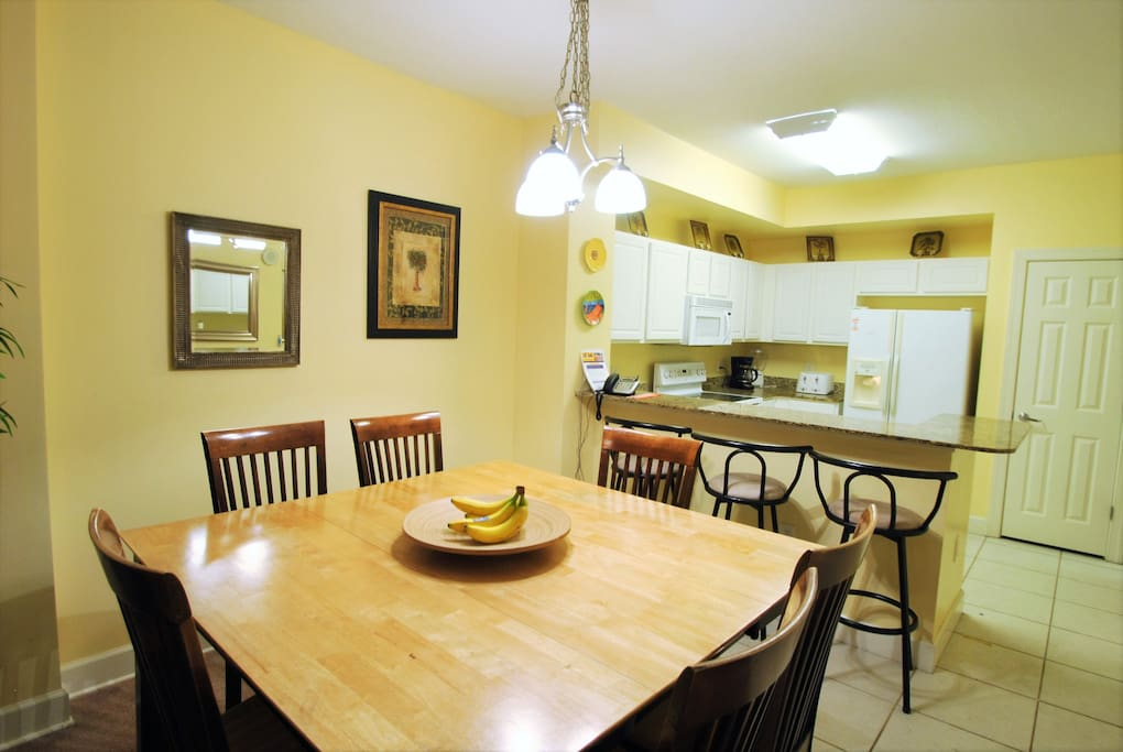 Dining table viewed from living area toward kitchen, bright beach colors throughout this condo