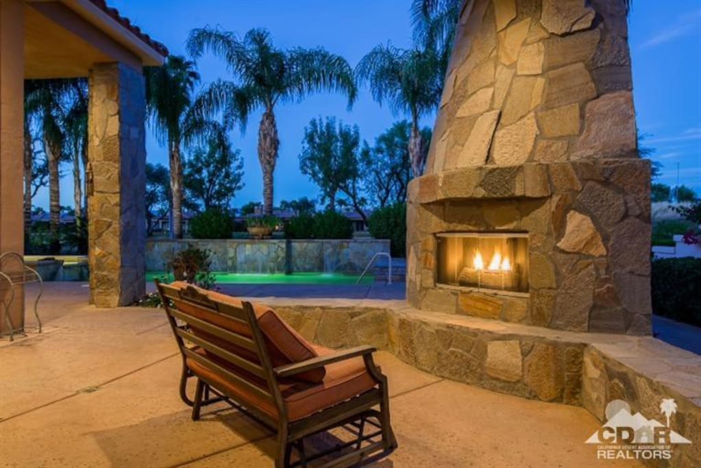 Backyard with fireplace, pool and golf course within a few feet.