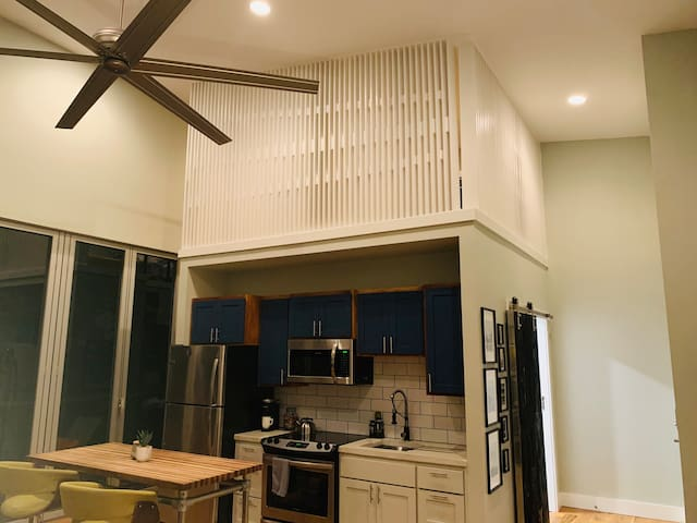 """Kitchen equipped with stainless fridge, electric range and over the range microwave.  """"Birdnest"""" loft is above with queen bed."""