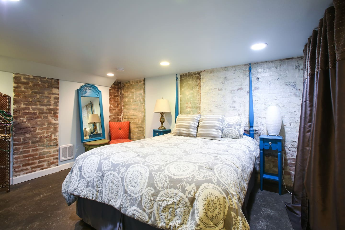 Lovely bedroom with queen bed, black out curtains, and lots of antique brick.