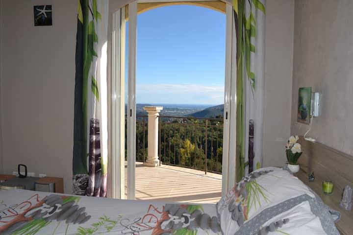 Chambre dans villa, piscine couverte, vue mer.