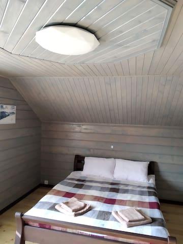 Дерев'яне ліжко із зручним матрацом та білосніжною постільною білизною.
