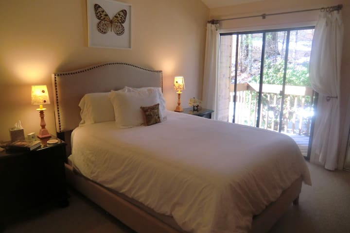 Guest  bedroom with private balcony & forest view.