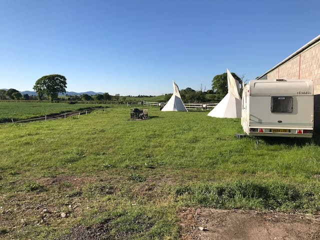 View from camp site entrance, track on left and fence at rear are the boundaries. Photo shows caravan, bbq and seating and tipis.
