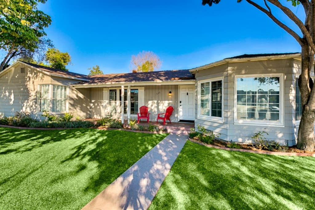 """Spacious Lawn Frames the Entry With Seating on the """"Front Porch""""."""
