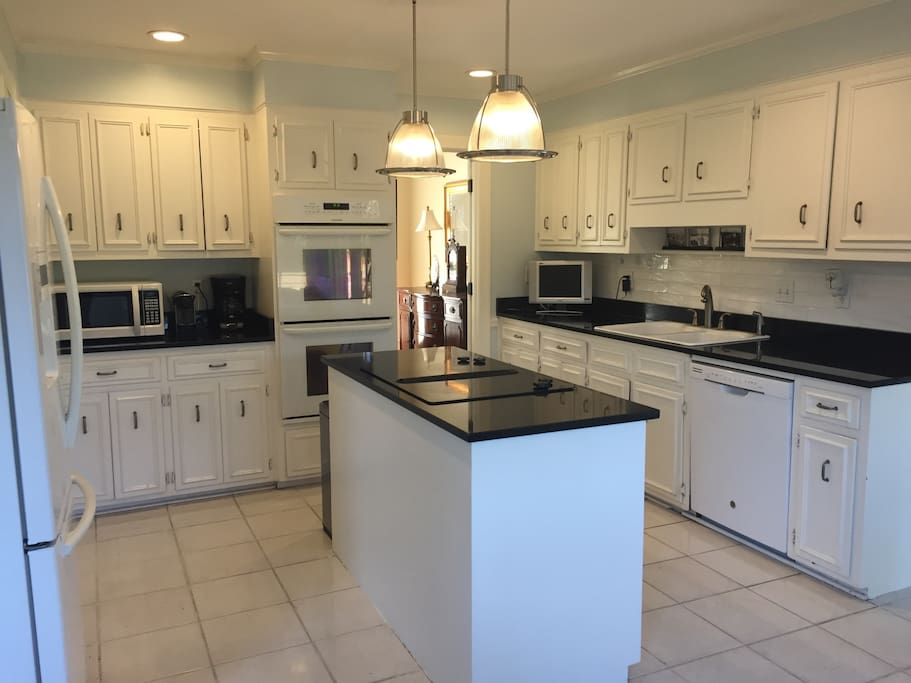 Kitchen with granite counters, double oven, microwave, coffee maker, tv