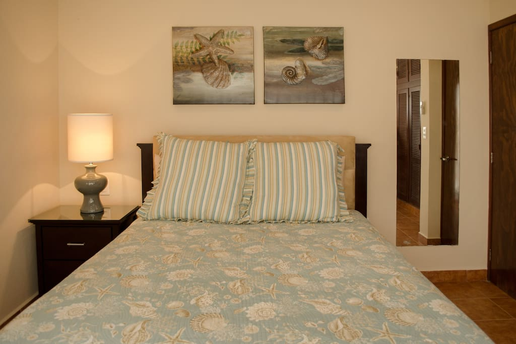 Luxurious queen guest  bedroom with large  closet, opens to  vistas of the pool