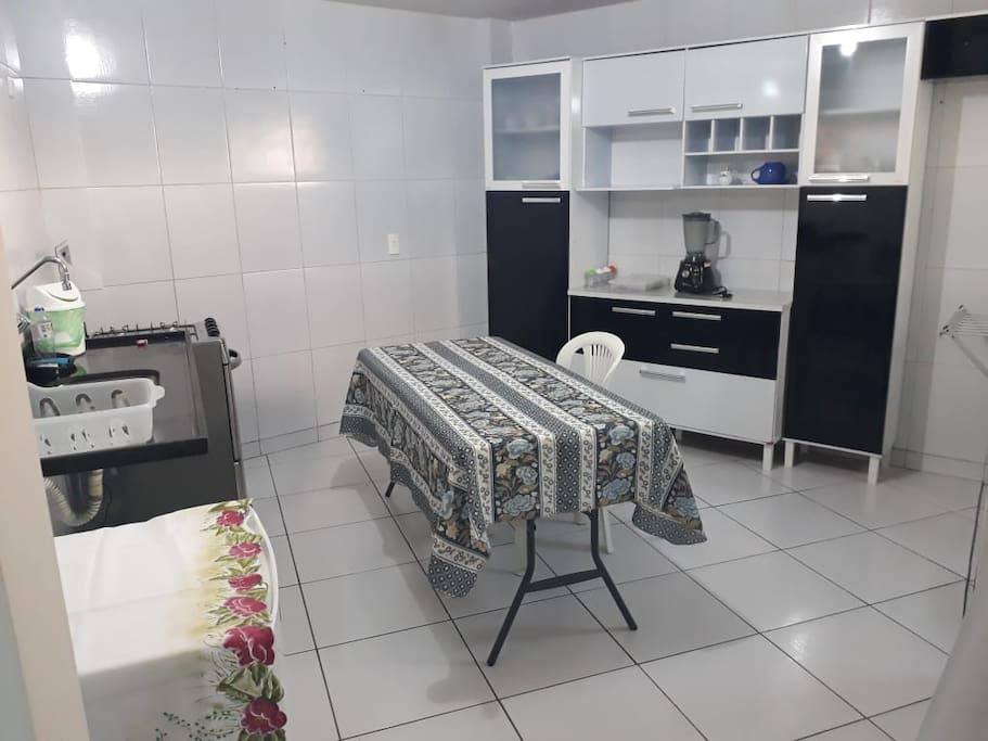 Cozinha com: fogão, geladeira pequena, mesa e armário