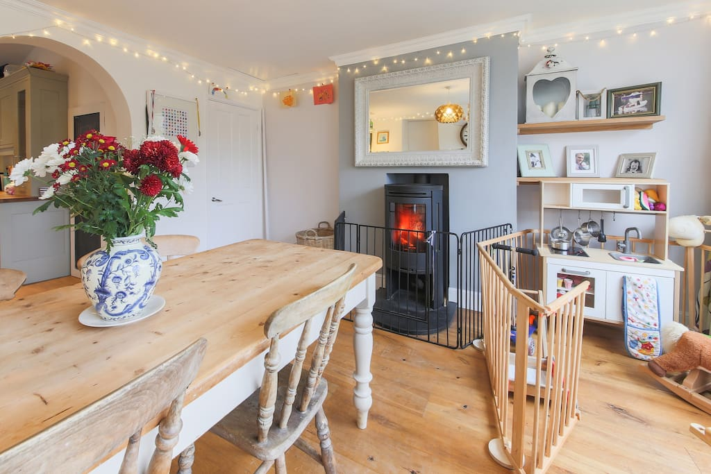 Open plan Kitchen Diner - Wood burner, kids play pen with lots of toys, kitchen and blackboard.