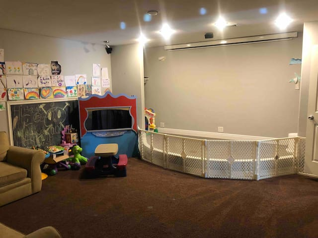 Movie theatre and playroom with child proof option.  The puppet theatre, toys, and art wall will keep them entertained for hours.  The room is also baby friendly with outlet covers and a baby gate option.