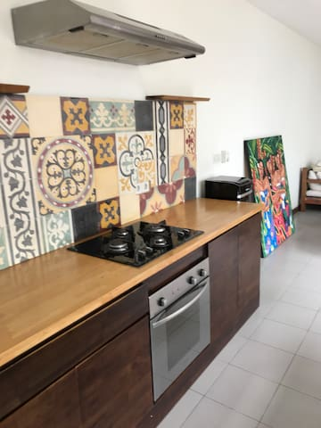 Fully equipped kitchen with stove, oven, dishes, cutlery, pots