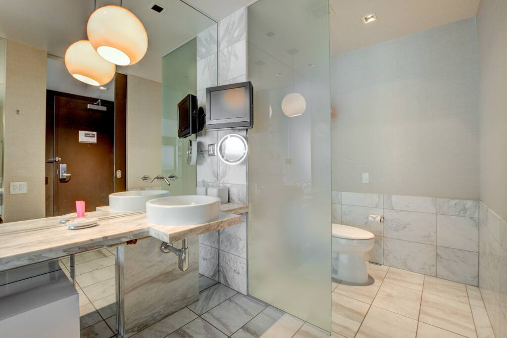 All marble bathroom with vanity makeup mirror and television!